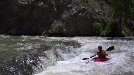 wide shot of small waterfall and man in Whitewater kayak