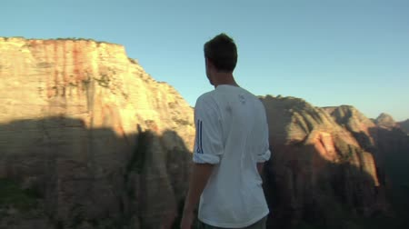 Man standing on mountain cliff, taking in view Wideo