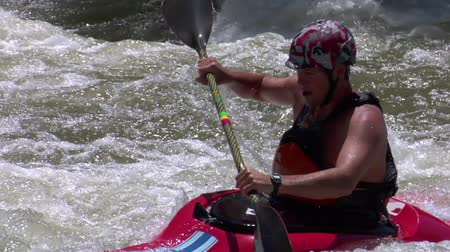 extreme close up on man paddling white-water kayak in slow motion