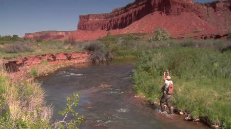 рыболовство : fly fisherman catches trout with red rock cliffs in distance Стоковые видеозаписи