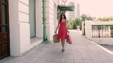 fashion outlet : Fair-skinned young woman walking down the street with her shopping bags Stock Footage
