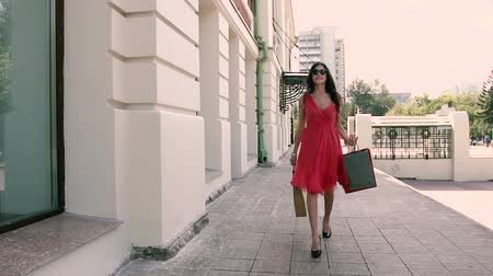 fashion outlet : Charming young woman walking downtown with her shopping bags