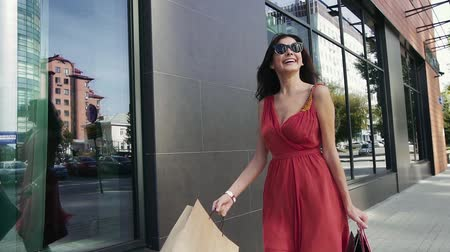 pitka : Attractive young woman walking happily downtown with shopping bags. Slow motion Dostupné videozáznamy