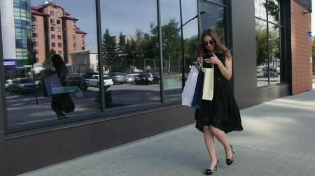 покупатель : Happy young woman enjoying her weekend shopping. Slow motion