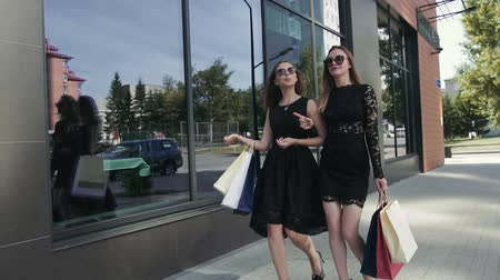 exited : Two beautiful female friends walking after shopping