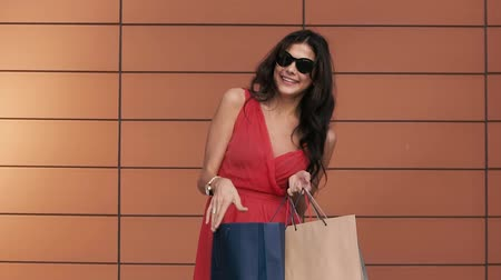 pitka : Attractive young woman looking into her shopping bag shines with happiness
