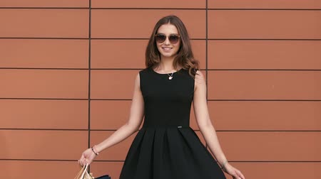 milan fashion : Cheerful shopping woman in black dress with shopping bags