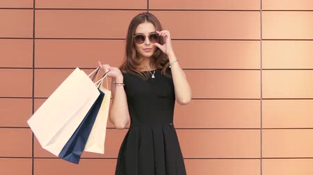 плечи : Pretty young girl walking in holding shopping bags. Slow motion Стоковые видеозаписи