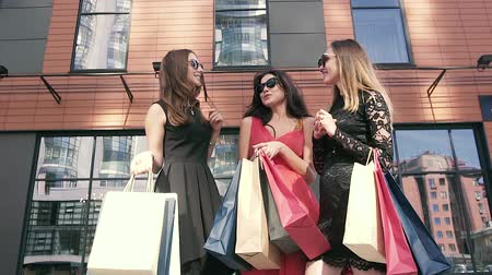 self promotion : Three beautiful ladies discussing their shopping day outdoors. Slow motion