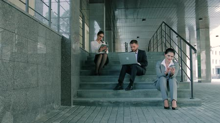 スクローリング : Young and attractive business people working on stairs using laptop, tablet and smartphone 動画素材