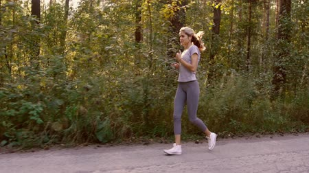 fitness tracker : Young blond woman jogging fast in the forest and enjoying the views of nature Stock Footage