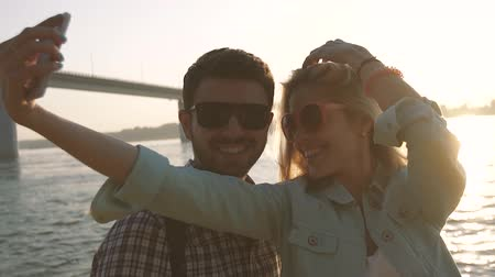 ひげを剃っていない : Loving traveling couple taking selfie against river and bridge