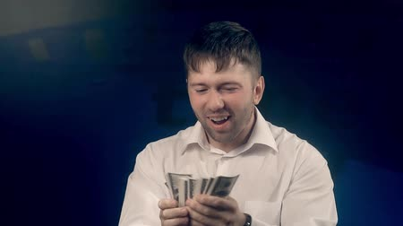 exibindo : Happy man feels delight looking through a roll of bills Stock Footage