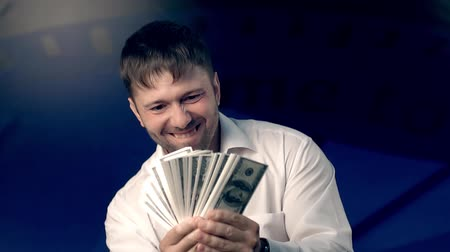 ganancioso : Happy young man waving money in his hands