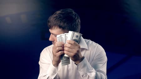 gritar : Young man looks back while counting a big amount of money