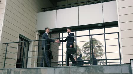prive jet : Two business men meeting at the entrance of business center and shaking hands to greet each other