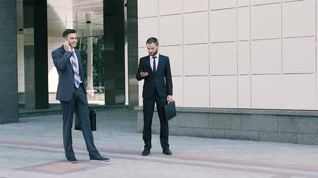 bossy : Two business men working outdoors at the middle of working day
