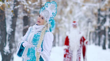 maiden : Beautiful Snow Maiden in the foreground playing with her hair and Father Frost in the background