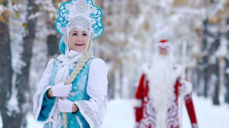 ded : Attractive woman dressed in Snow Maiden costume in the foreground smiling Stock Footage