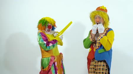 színésznő : Short funny clown scares the other clown with huge scissors