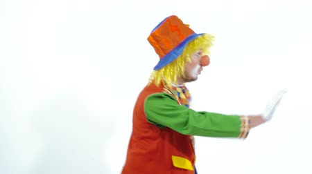 scary clown : Funny clown walking backward showing colorful box and smiling in surprise Stock Footage