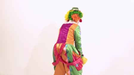 serpentyny : Funny female clown dancing in a comical way against white background