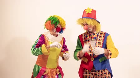 Октоберфест : Two playing clowns having fun and trying to blow soap bubbles Стоковые видеозаписи