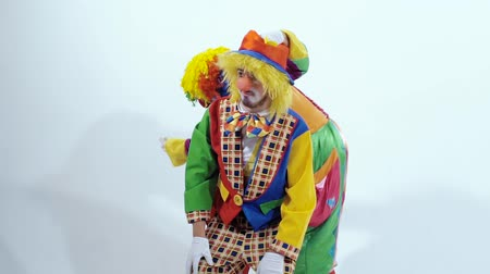 traje de passeio : Close-up of two happy clowns one of which is jumping backward around the other clown