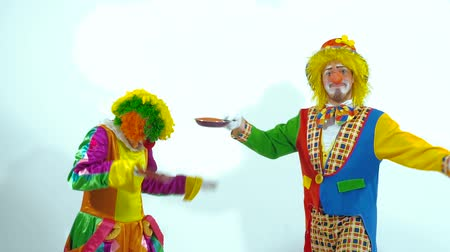 insincere : A couple of circus clowns throwing up toy-pancakes and trying to catch them
