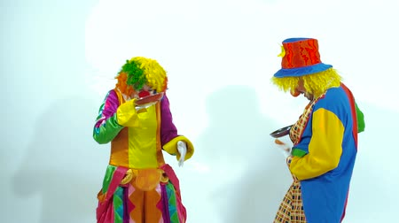scary clown : Two funny clowns trying to catch pancakes. Slow motion Stock Footage