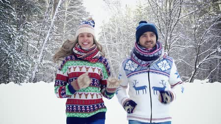 Young pretty couple jogging together in the winter forest