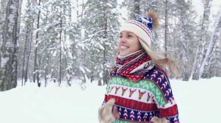 Attractive blond woman jogging in the forest on a winter day