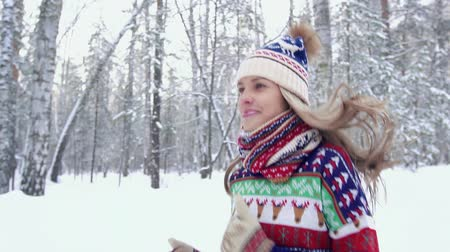 Portrait of happy young woman running in the forest in winter