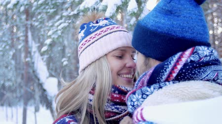 Close-up of young lovely couple kissing in winter forest