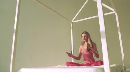 sitting floor : Yoga woman in bed meditating in lotus pose Stock Footage