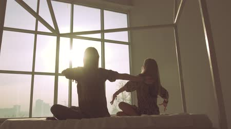 Two slender women doing yoga against window background