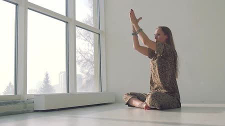 Young calm woman doing yoga in well-lit studio