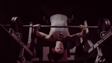 Young fit sportsman doing barbell bench pressing while exercising