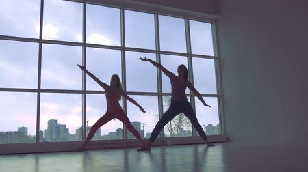 Two slender yoga women practicing extended triangle pose in the studio with natural light