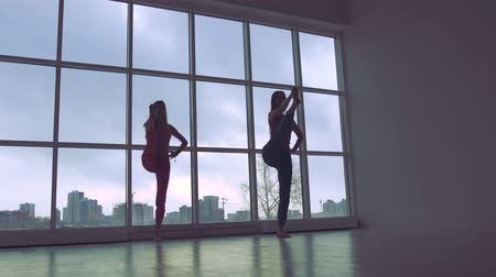 Two lovely women practicing yoga poses together in white studio with natural light Stock Footage