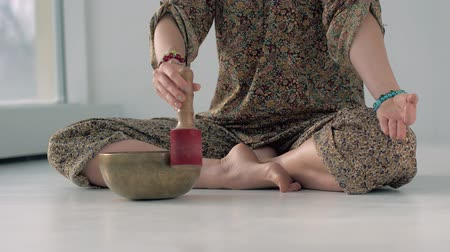 Close-up of yoga woman playing a singing bowl