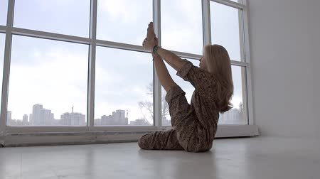 Young woman practicing yoga and stretching leg up