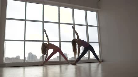Beautifully-shot young women practicing extended triangle yoga pose together