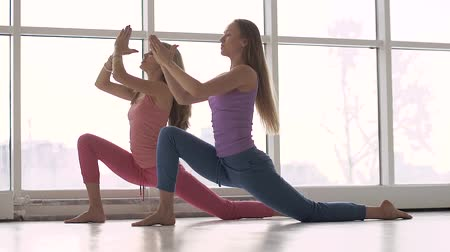 Pretty young women in comfortable sports clothing doing yoga