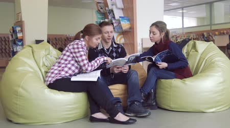 könyvesbolt : University students in library discussing articles from their books