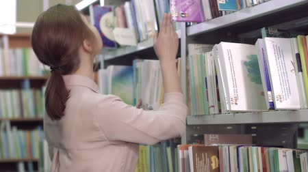 schoolboeken : Portrait of focused college girl looking for a book among bookcases