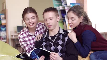 profesor : Smiling university students in library reading a book together