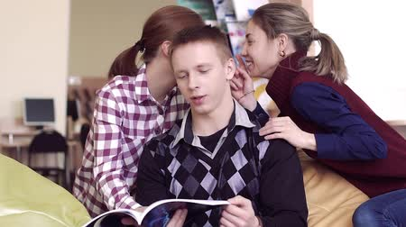cheerfulness : College boy reading in library sitting with two laughing college girls Stock Footage