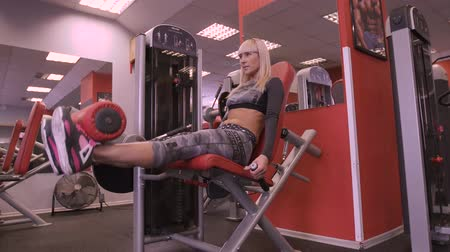 squats : The girl is exercising in the gym