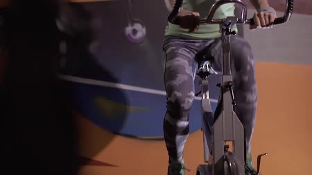 stationary : Young caucasian woman in sportswear working out on stationary bicycle Stock Footage